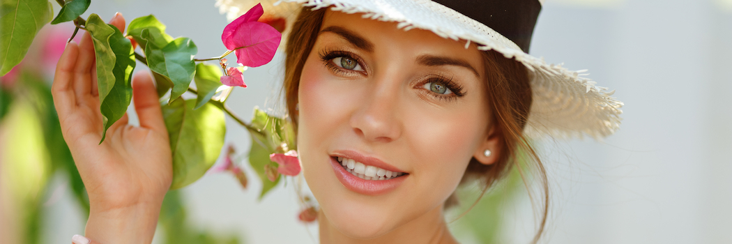 Close up of a woman wearing a hat and smelling flowers