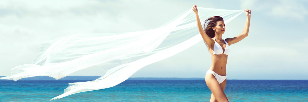 woman on beach with arms in the air
